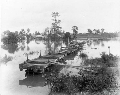 Flat wagons set up as a temporary bridge between Milton and Toowong, c1900