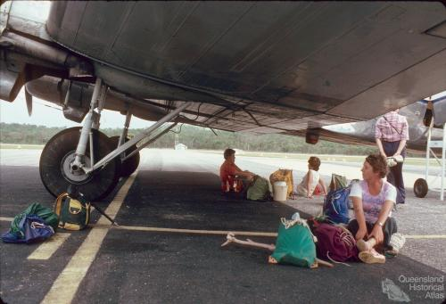 Passengers sitting in the shade of an Air Queensland DC3, Lockhart Airport, 1982