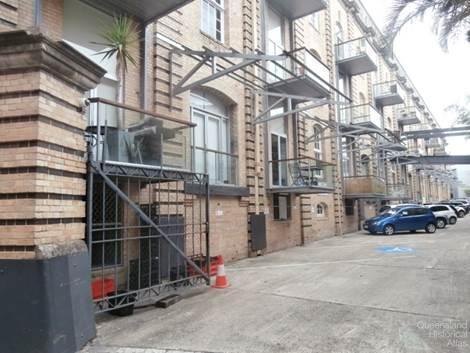 Apartment balconies facing car park of AML&F wool stores, 2014