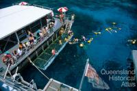 Tourists diving from a pontoon on the Outer Barrier Reef, 1991